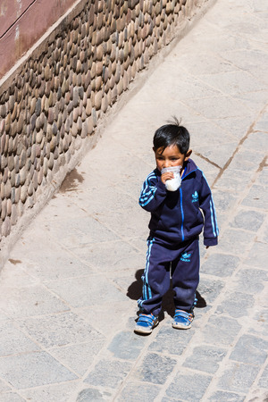 pisac: Pisac, Peru - May 15: Young boy walking dressed up in full Adidas clothing in the Sacred Valley Market. May 15 2016, Pisac Peru. Editorial