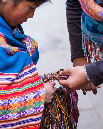 pisac: Pisac, Peru - May 15: Adorable native Quechua girl walking the alleyways selling hand made souvenirs in the Sacred Valley Market. May 15 2016, Pisac Peru.