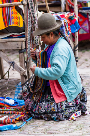 pisac: Pisac, Peru - May 15: Quechua woman organizing her booth  in the Sacred Valley Market. May 15 2016, Pisac Peru.