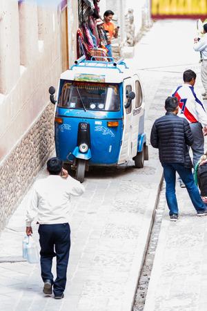 pisac: Pisac, Peru - May 15: MotoTaxi a small compact vehicle making its way thru the Pisac market. May 15 2016, Pisac Peru. Editorial
