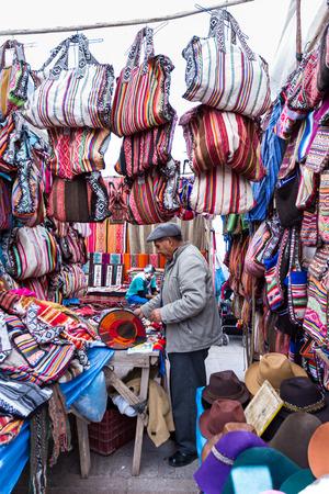 pisac: Pisac, Peru - May 15: Peruvian man selling souvenirs like handbags and hats at the market in Pisac. May 15 2016, Pisac Peru. Editorial