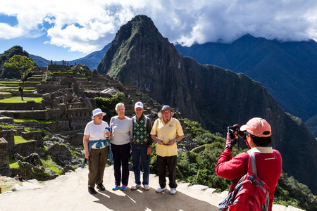 the lost city of the incas: Machu Pichu, Peru - May 16 : Tourists posing with The lost City of the Incas in the background. May 16 2016, Machu Pichu Peru.