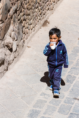 adidas: Pisac, Peru - May 15: Young boy walking dressed up in full Adidas clothing in the Sacred Valley Market. May 15 2016, Pisac Peru. Editorial