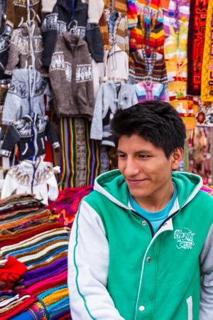 Pisac, Peru - May 15: Peruvian man selling souvenirs like clothing and textiles at the market in Pisac. May 15 2016, Pisac Peru.