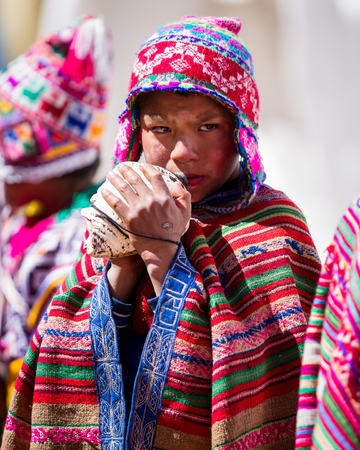 pisac: Pisac, Peru - May 15: Young man playing a tune using a conch shell as part of a ceremony in the Sacred Valley Market. May 15 2016, Pisac Peru. Editorial