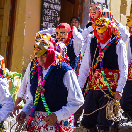 religious clothing: Ollantaytambo, Peru - May 16 : Religious celebration for Fiestas de Pentecostes with people wearing masks and colorful clothing on the streets of Ollantaytambo. May 16 2016, Ollantaytambo Peru.
