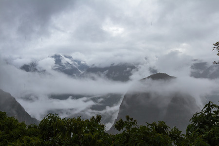 clinging: beautiful view of the peaks surrounding Machu Pichu with fog and clouds clinging on to them in a rainy morning