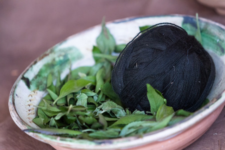 close up of a ball of black yarn in a bowl with the leaves used to obtain the color