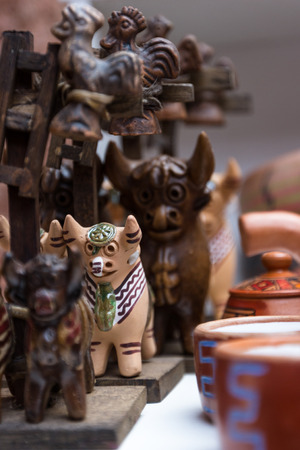 belief systems: close up of a traditional Peruvian roof ornament with bulls and a cross
