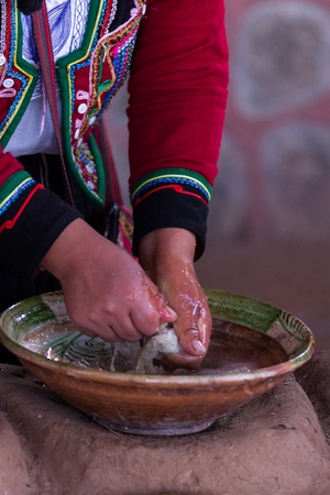 weavers: Close up of a native Peruvian woman showing traditional methods for washing textiles