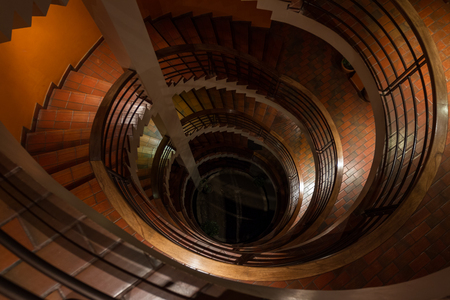 view of a spiral staircase from top to bottom with very little light