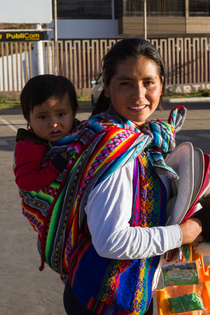 native american baby: Cusco, Peru - May 11 : Young mother and her baby dressed in traditional very colorful  Cusco clothing selling coca caramel to help with elevation sickness. May 11 2016, Cusco, Peru. Editorial