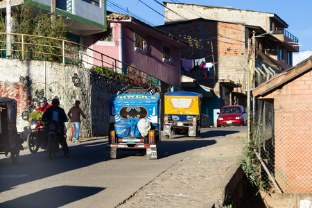three wheeler: Peru - May 17 : Three wheeler taxi decorated with a Barman sticker going up a hill in Peru . May 17 2016, Peru.