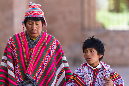 pisac: Pisac, Peru - May 15: Quechua Man walking with his son dressed in beautiful traditional clothing in the Pisac Market. May 15 2016, Pisac Peru. Editorial