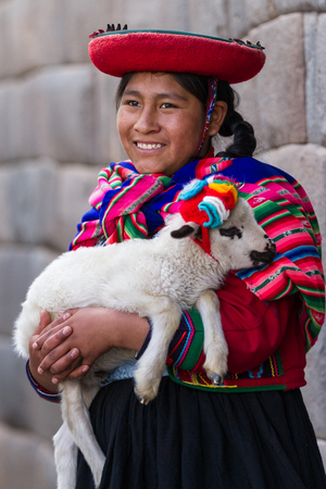 Cusco, Peru - May 14 : Jenni, a young woman dressed in colorful traditional native Peruvian closing holding a baby Lamb with Inca walls in the background. May 14 2016, Cusco Peru. Editorial