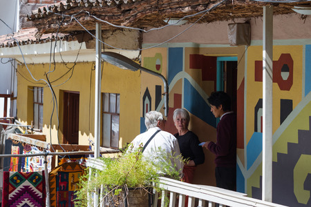 pisac: Pisac, Peru - May 15: Couple ordering lunch on an open air balcony overlooking the Pisac Market. May 15 2016, Pisac Peru.
