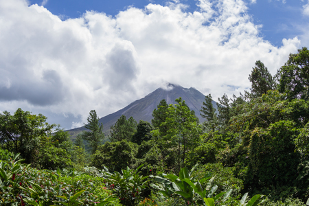 fortuna: classic cone shape volcano surrounded by lush tropical vegetation and fast moving clouds in La Fortuna de San Carlos, Costa Rica Stock Photo