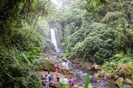 Alajuela, Costa Rica - May 02: families and friends enjoying the view of a beautiful waterfall in the rainforest. May 02 2016 Alajuela, Costa Rica.
