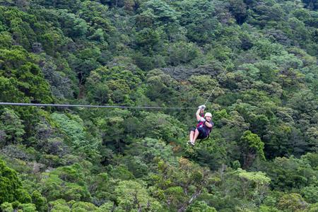 젊은 남자가 구름을 통해 확대 zip 라인에 모험 몬테 베르데 코스타리카
