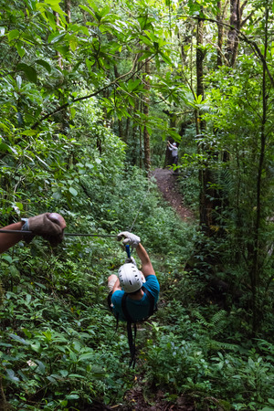 young man zooming thru a cloud forest on a zip line adventure in Monteverde Costa Rica Stock Photo