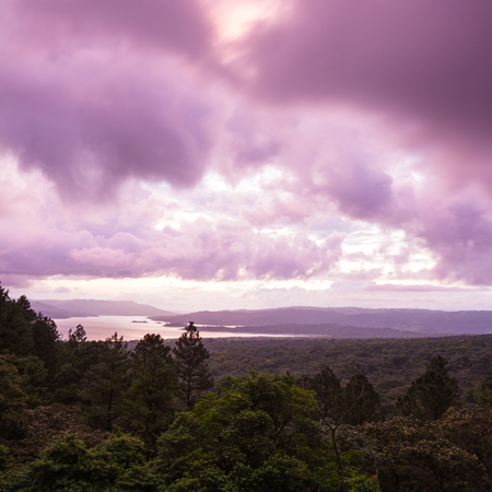 sunsetting behind Lake Arenal viewed from an elevated viewpoint above the tree tops Stock Photo