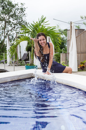 turismo ecologico: young playful woman sitting on an outdoors hot tub in Costa Rica