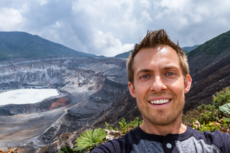 self discovery: young male taking a self portrait with the Poas Volcano in the Background Stock Photo