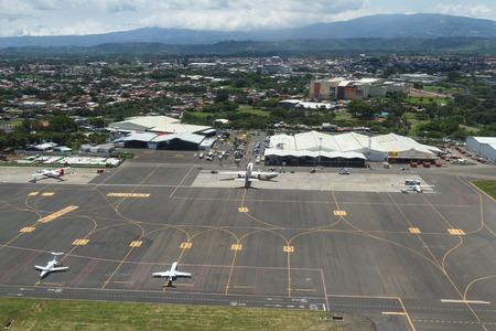 San José, Costa Rica - 24 de mayo: vista aérea de un área de mantenimiento y espera del aeropuerto internacional desde el interior de un pequeño avión. 24 de mayo 2016, San José Costa Rica. Foto de archivo - 64755258