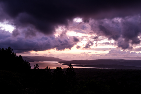 sunsetting behind Lake Arenal viewed from an elevated viewpoint above the tree tops Editorial