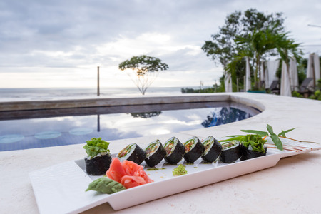 close cup of a vegetarian sushi roll served poolside on a white plate Editorial