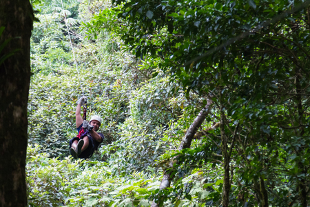 zooming: young man zooming thru a cloud forest on a zip line adventure in Monteverde Costa Rica Stock Photo