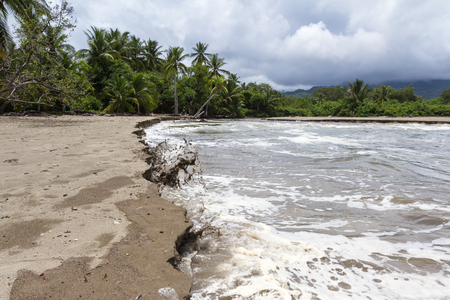 merging: small river merging with the pacific ocean in the Costa Rican south pacific Stock Photo