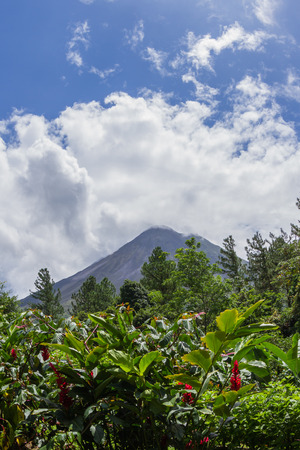 classic cone shape volcano surrounded by lush tropical vegetation and fast moving clouds in La Fortuna de San Carlos, Costa Rica Stock Photo