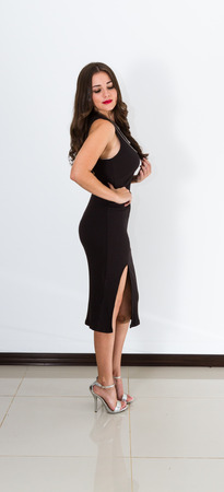 beautiful young Costa Rican woman wearing a sexy black dress over a white background