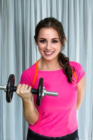 young woman portrait in workout clothing lifting weights indoor