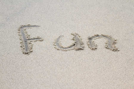 compacted: the word fun written on sand in a tropical relaxing beach