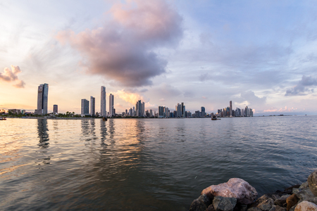 Panama City, Panama: Cityscape from across the bay with colorful sunset colors on the clouds.