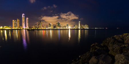 Panama City, Panama: Twilight Cityscape from across the bay in Panama with a serene reflection on the water. Stock Photo