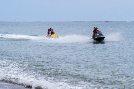 Santa Clara, Panama- June 10: tourists enjoying a thrill ride being pulled by a wave runner on the beach. June 10 2016, Santa Clara, Panama. Editorial