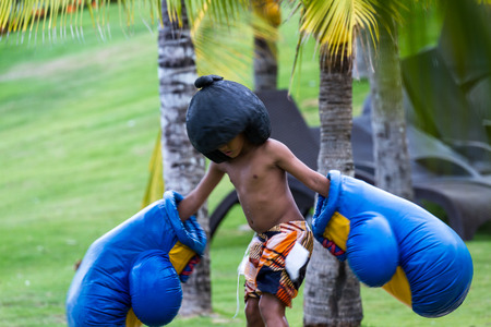 oversized: Santa Clara, Panama- June 12: Young boy wearing oversized boxing gloves and a helmet in a Hotel in Panama. June 12 2016, Santa Clara, Panama.