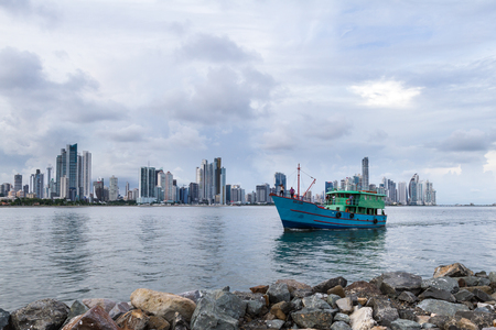 work boat: Panama City, Panama- June 08: Fishing boat and crew coming in after a days work with the city in the background. June 08 2016, Panama City, Panama.