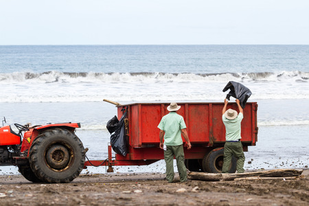 Tambor, Costa Rica - June 25: Hotel employees cleaning up the beach after a strom. June 25 2016, Tambor, Costa Rica.