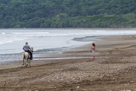 guia de turismo: Tambor, Costa Rica - 20 junio: La guía turística en un caballo disfrutando de la vista. 20 junio de 2016, Tambor, Costa Rica.