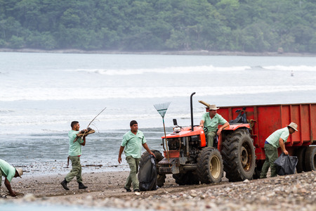 strom: Tambor, Costa Rica - June 25: Hotel employees cleaning up the beach after a strom. June 25 2016, Tambor, Costa Rica.