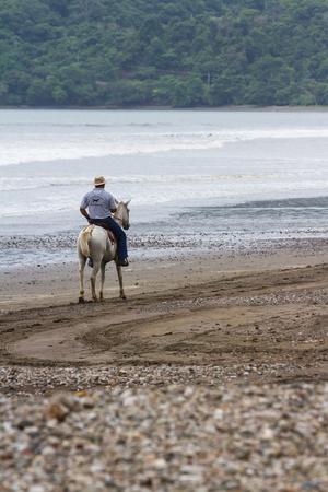 tour guide: Tambor, Costa Rica - June 20: Tour guide on a horse enjoying the view. June 20 2016, Tambor, Costa Rica.