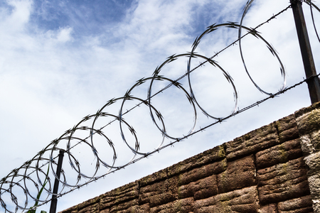 razor and barbed wire with a cloudy sky in the background