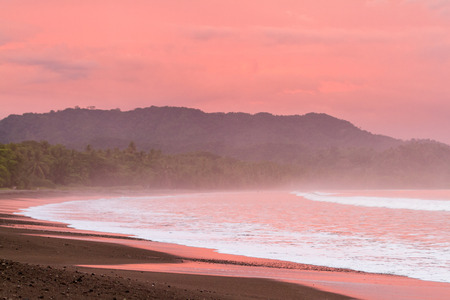 sooth: Beautiful sunset on a beach in Costa Rica with amazing vivd color in the clouds and also reflecting on the sand and water