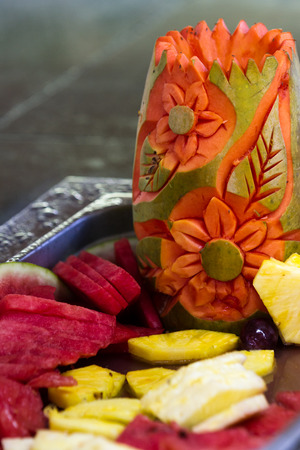 papaya flower: tropical fruit carved into flowers and leaves as a center piece for a buffet