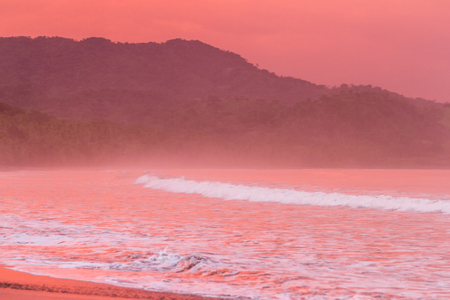 Beautiful sunset on a beach in Costa Rica with amazing vivd color in the clouds and also reflecting on the sand and water