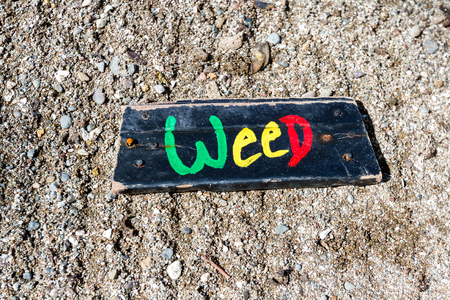 piece of drift wood with rusty nails and the word weed painted on it found in the pacific coast of Costa Rica Stock Photo
